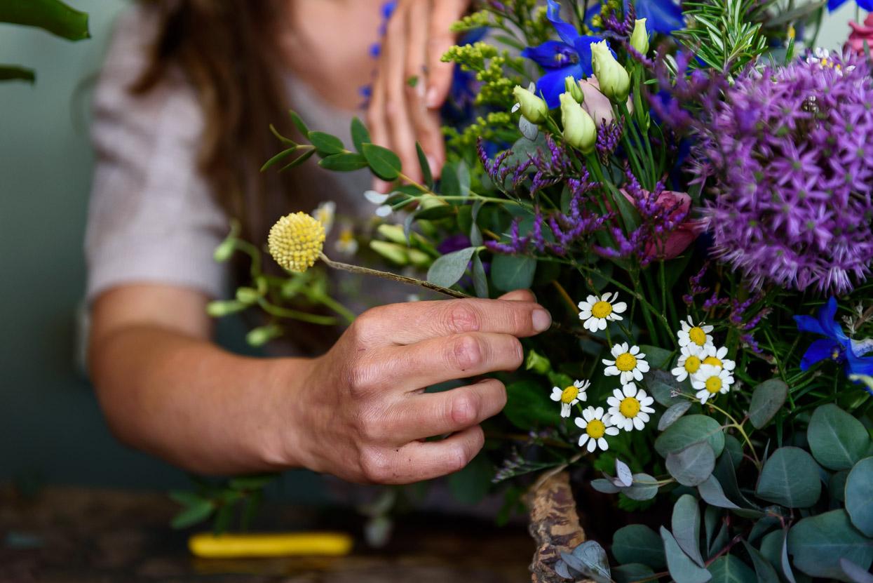 hand bij bloemstuk